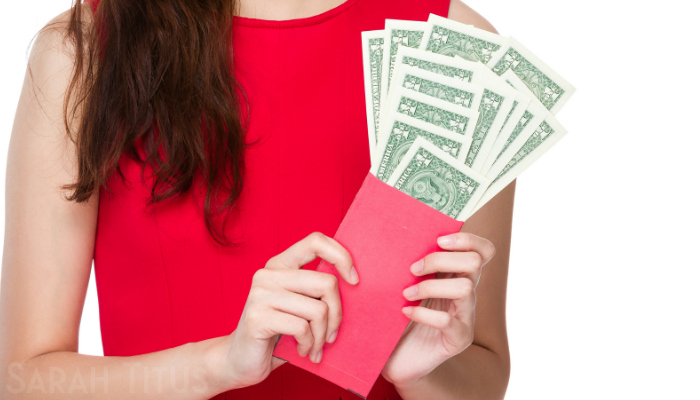 Woman in a red dress showing all the one dollar bills she saved this year