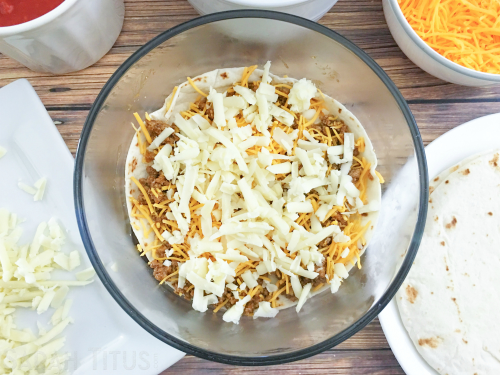 Ingredients for the taco bake: salsa, cheeses and tortillas with the beef, a tortilla and the cheeses layered on the bottom of a glass bowl