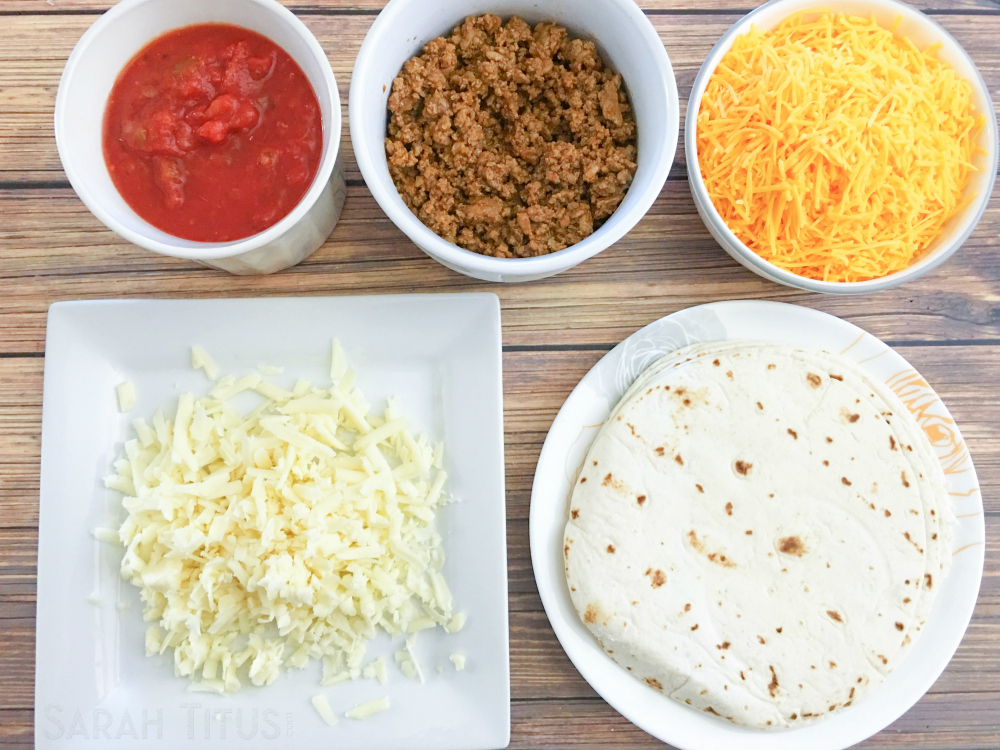 Ingredients for the taco bake: salsa, beef, cheeses and tortillas on a wooden table