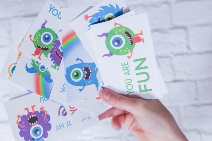 Mom holding adorable, colorful, printable monster Valentine's Day cards for kids