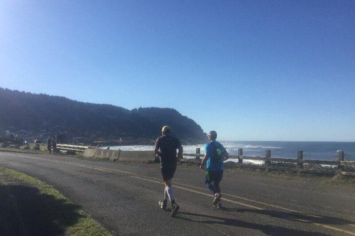 Two runners on the road by the beach