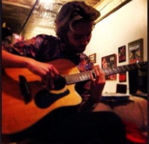 Toby Regbo suona la chitarra