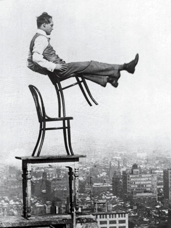 A man balancing on a Thonet chair, c. 1900