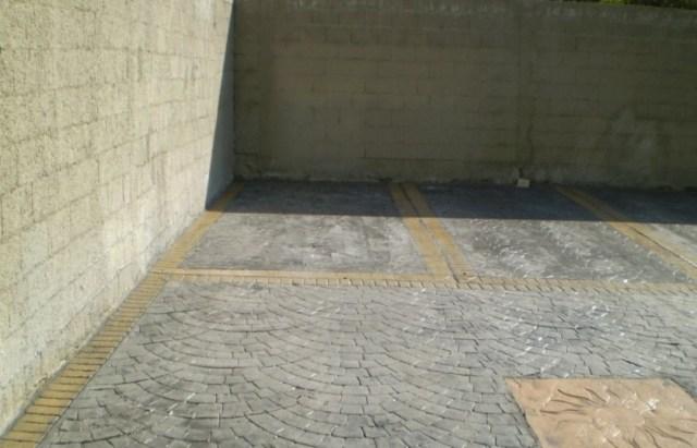 Piazzale condominiale realizzato in cemento stampato sanpietrini con greche colorate presso cantiere Terralba