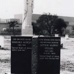 feature granite headstones and white marble Jesus statue