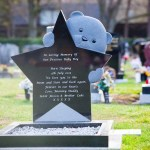 childs blue teddy bear peering over a star gravestone