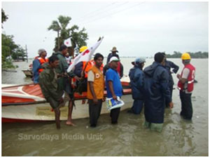 Sarvodaya officers load pigeon pea onto boats for delivery to Kothiapula School