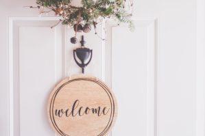 Round Wooden Welcome Sign on Door