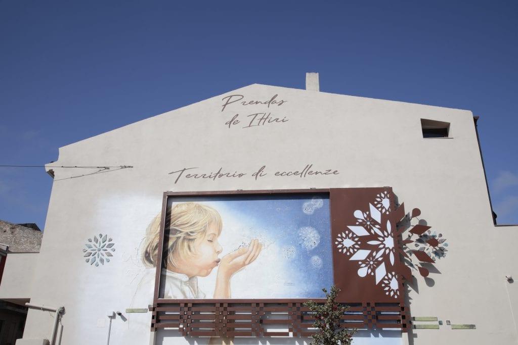 L'arte omaggia i 15 anni di Prendas de Ittiri e il muro della piazza diventa un quadro