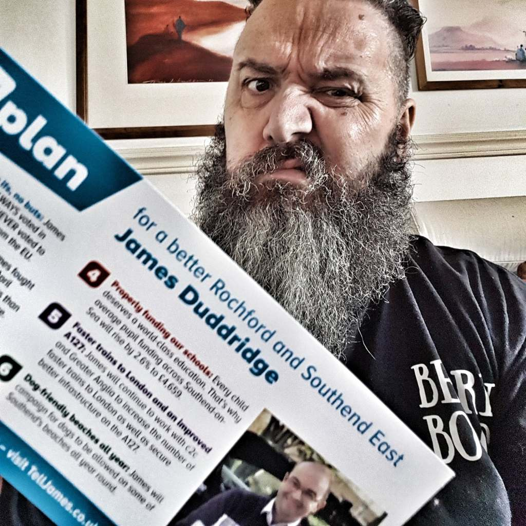 General Election Tory leaflet held by disabled man with beard
