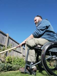 Me sat in my wheelchair in the garden with a hoe in my hands weeding some of the border.