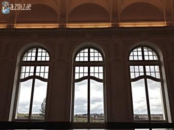 Durch drei große Fenster des Festsaals (dunkel) die Aussicht auf Marbach (hell) fotografiert
