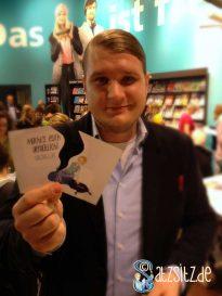 Viermalbe am Stand des frechverlags auf der Buchmesse: hält eine zerschnitte Postkarte hoch