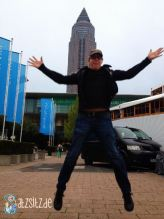 Frank Schmeisser hüpft lustig vor dem Frankfurter Messeturm hoch