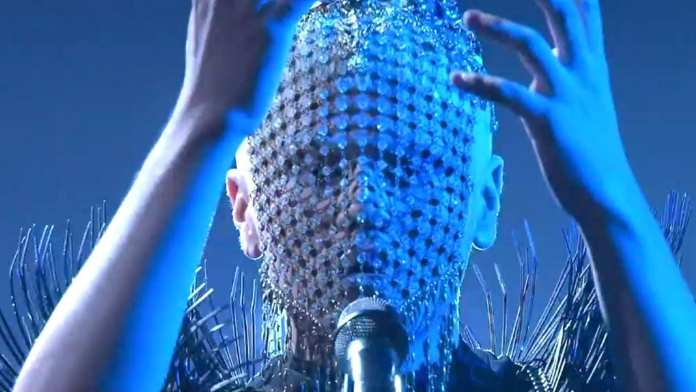 Glamorous and masked, Sheldon Riley perform on The Voice | Sausage Roll