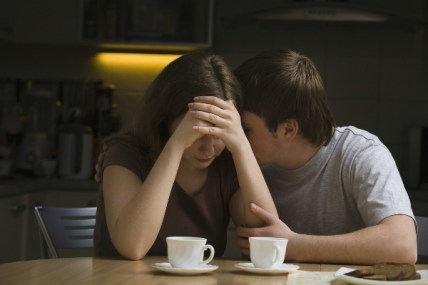 Young man consoling woman at dining table in house
