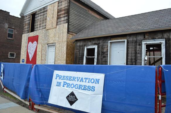 """Preservation in Progress"" signs were placed by members of Save CR Heritage on buildings in New Bohemia where restoration is ongoing nearly five years after the Floods of 2008. (photo/Cindy Hadish)"