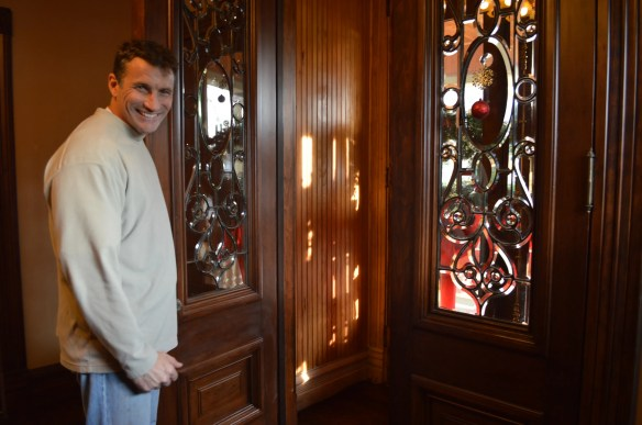 Mark Cardis opens the front door to the home he is restoring in Cedar Rapids. While Cardis tries to keep the architecture authentic, some features, such as these doors were replaced if beyond repair. (photo/Cindy Hadish)