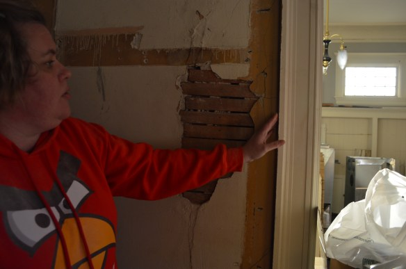 Dawn Stephens takes a closer look at a wall where a closet had been added when the home became a four-plex. She and her husband are returning the home to its original floor plan. (photo/Cindy Hadish)