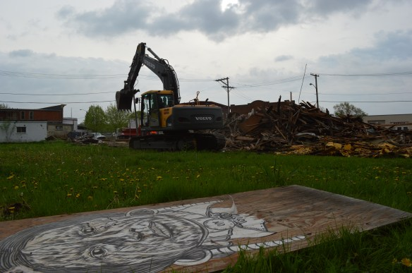 Artwork painted on the building, and other endangered buildings in the district, is shown on the ground next to the Hach Building as the structure was demolished on Monday, May 12, 2014, in the New Bohemia neighborhood of southeast Cedar Rapids. (photo/Cindy Hadish)