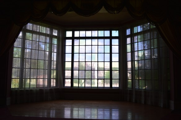 Renowned Iowa artist Grant Wood is credited for this window in the George B. Douglas mansion, which now looks out onto a view of the new PCI parking ramp near downtown Cedar Rapids. (photo/Cindy Hadish)