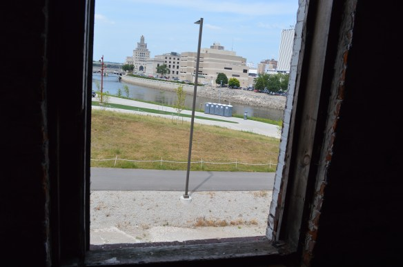 The former Cedar Rapids City Hall can be seen from a broken window in the Knutson Building, along the Cedar River in Cedar Rapids, Iowa. (photo/Cindy Hadish)