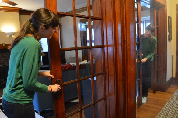 Liz Martin opens a pocket door in her home in Wellington Heights, one of many features that attracted her to the house. (photo/Cindy Hadish)