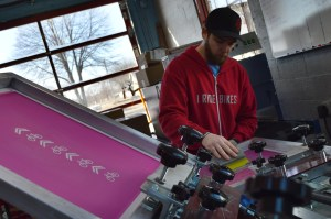 Tony Burnett prepares a T-shirt on the six-color screen printing press inside Red Ball Printing. (photo/Cindy Hadish)
