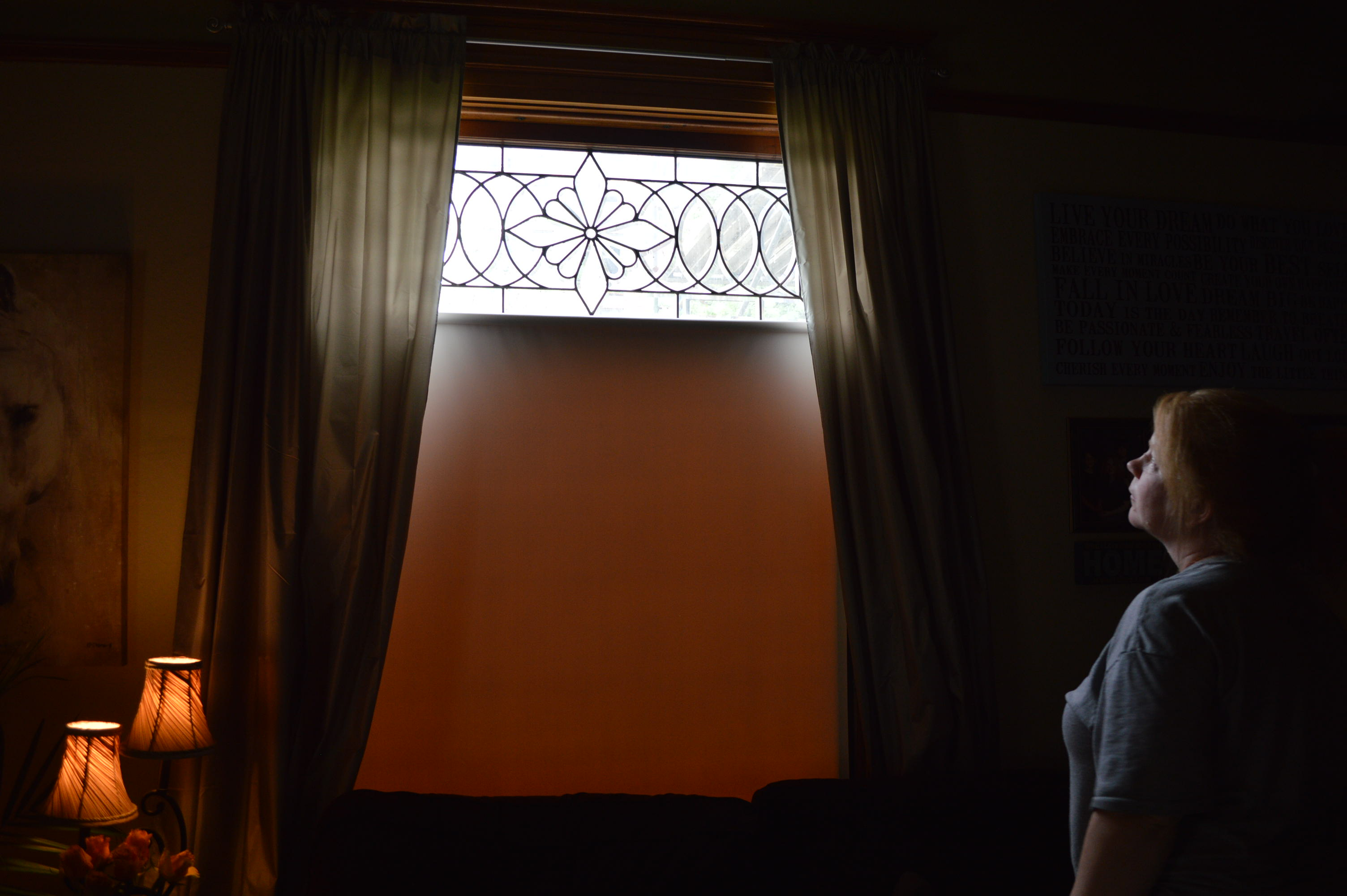 Tamara Dallege looks at a window of the Victorian house she purchased in southeast Cedar Rapids. She could face jail time that would jeopardize her teaching license if repairs are not made by Aug. 14, 2015. (photo/Cindy Hadish)