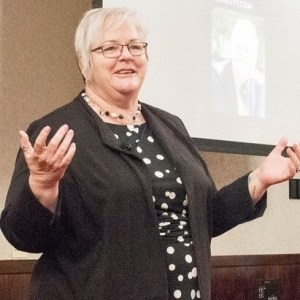 """Deb Brown speaking to a group, turns her hands palm up, as if to say """"who knows?"""""""