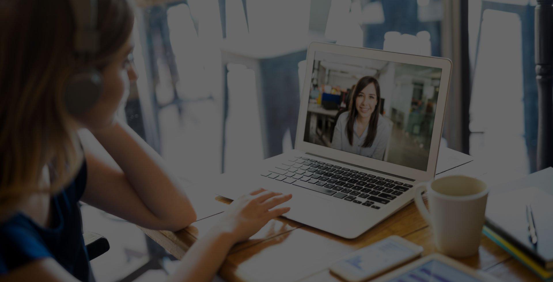 Woman on Laptop speaking to someone