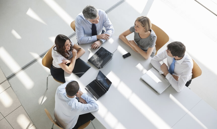 four people having a business meeting around a table