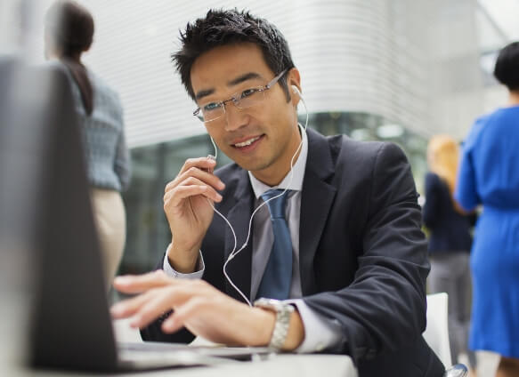 Japanese man in suit and glasses talking on a headset