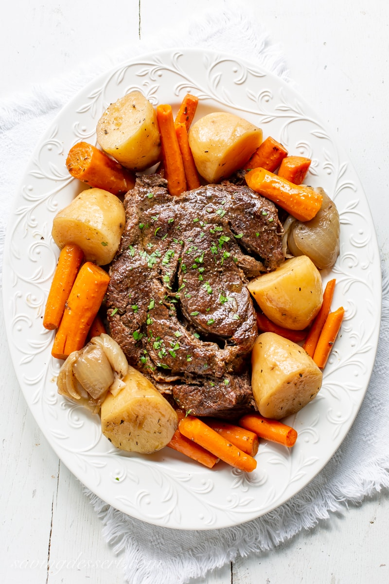 A platter with a slow cooker pot roast, potatoes, onions and carrots garnished with parsley