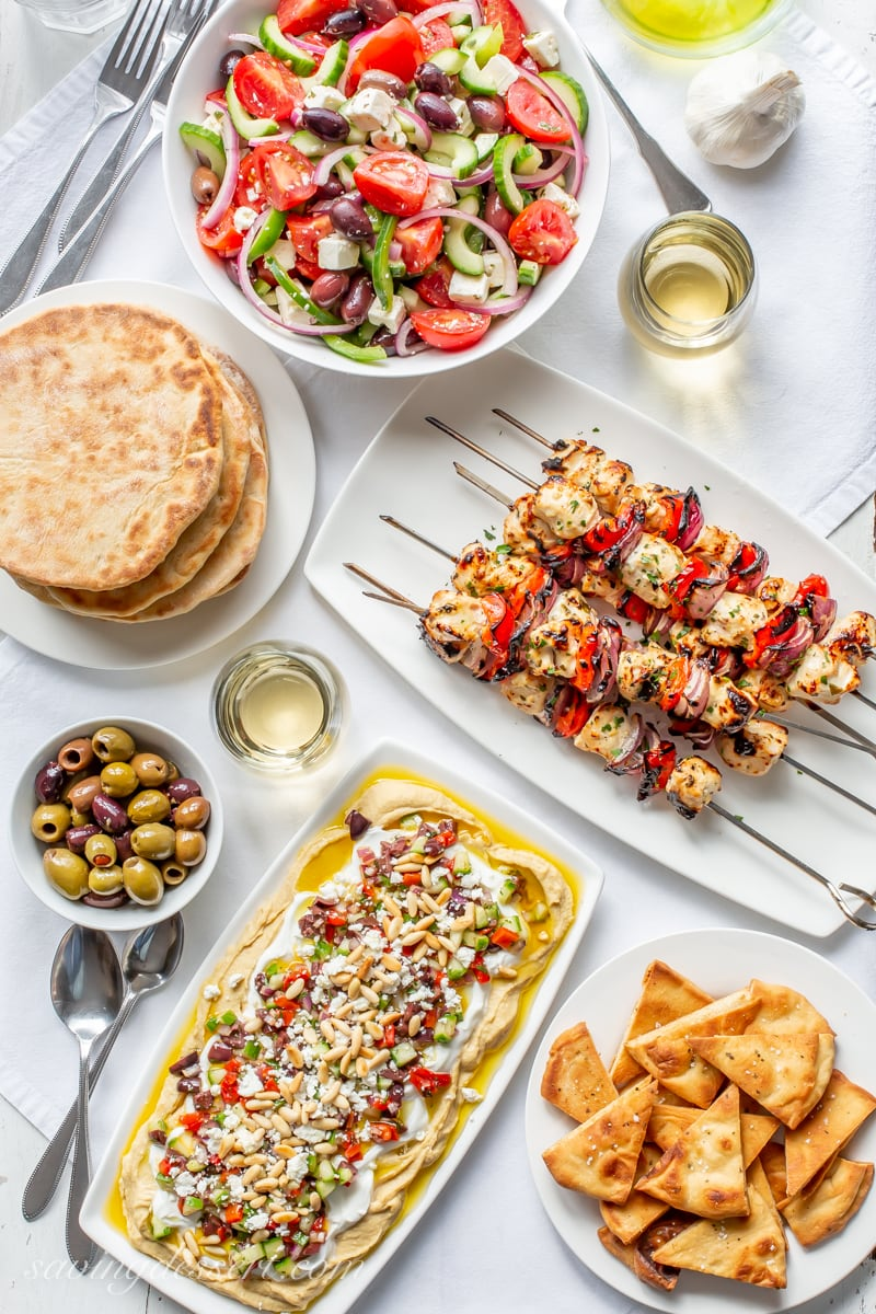 A table filled with Greek inspired recipes from homemade whole wheat pitas, Greek Salad and hummus dip with olives