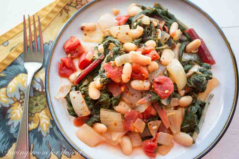 A plate with Swiss Chard, white bean, onion, and tomato stew with crushed red pepper