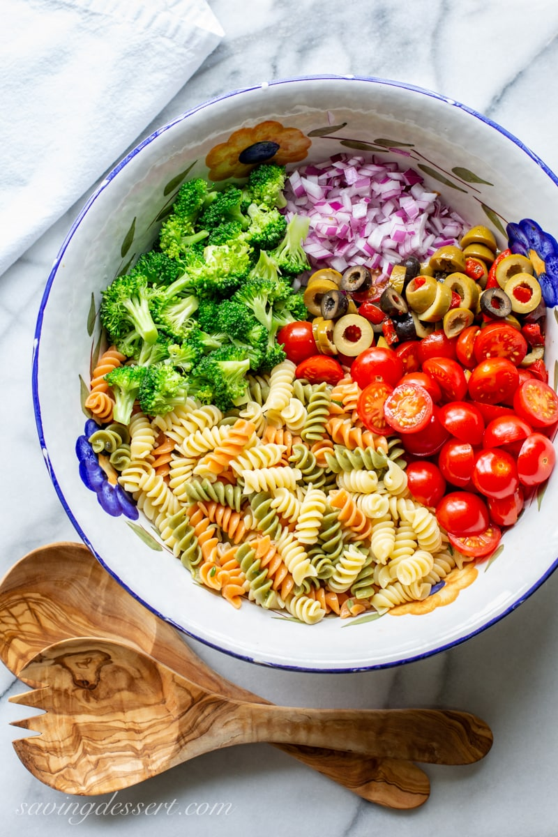 An overhead view of a big bowl of pasta noddles with broccoli, red onion, olives and tomatoes