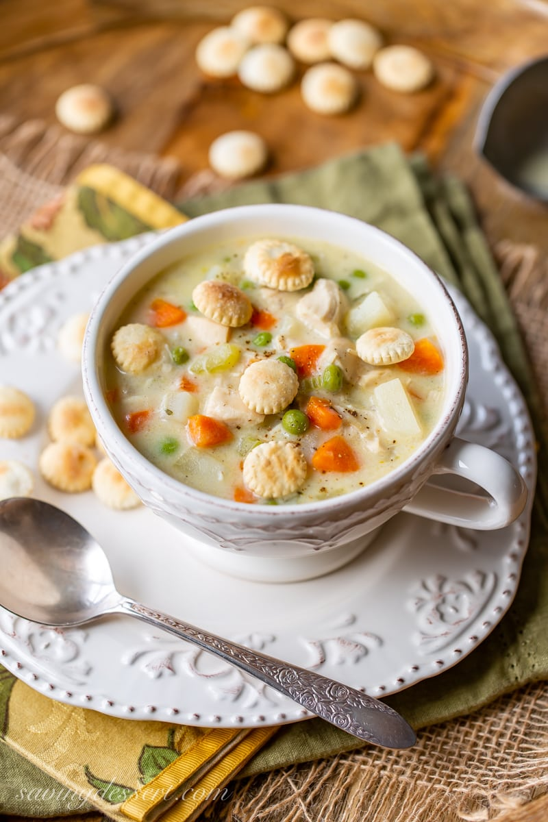 A cup of chicken pot pie soup with carrots, peas and oyster crackers