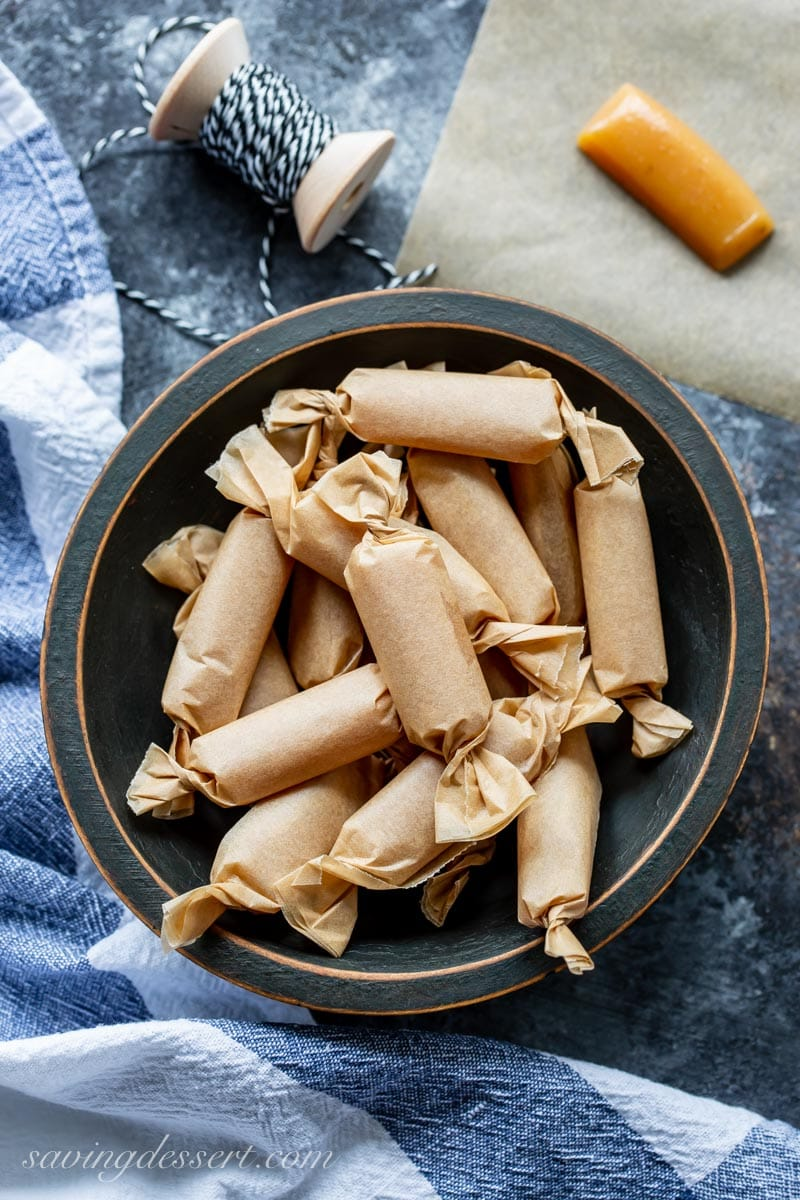 a bowl of wrapped apple cider caramels