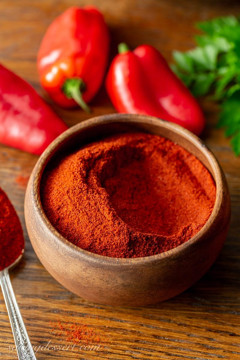 A wooden bowl of sweet Hungary paprika with red peppers and fresh parsley