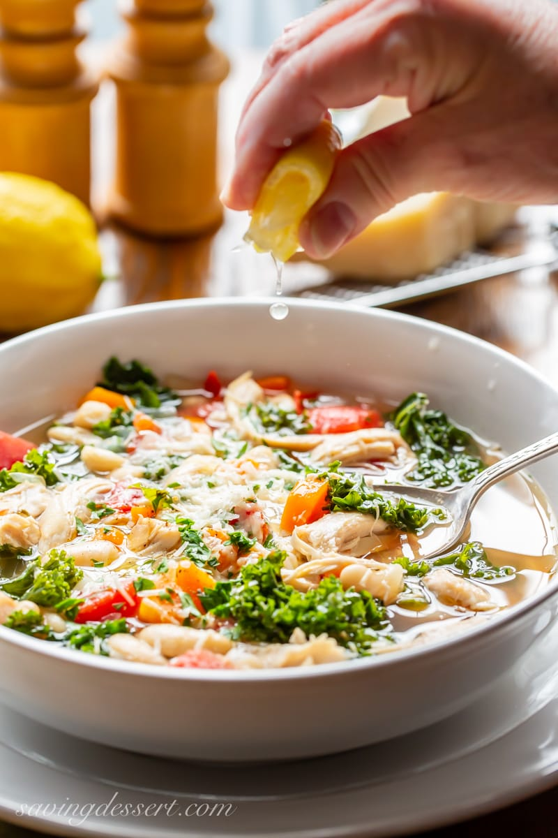 A bowl of chicken & White Bean Soup with kale and tomatoes topped with Parmesan and a squeeze of lemon juice