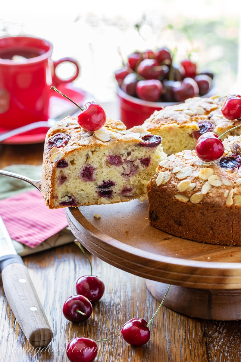 A sliced cherry breakfast cake with almonds and fresh cherries on top