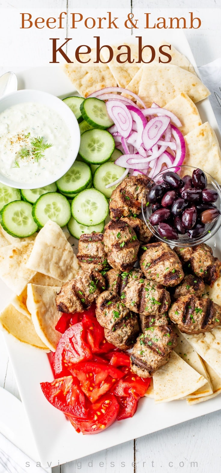 A tray with grilled lamb kebabs, tomatoes, cucumber, onion, pita wedges and cucumber-yogurt sauce