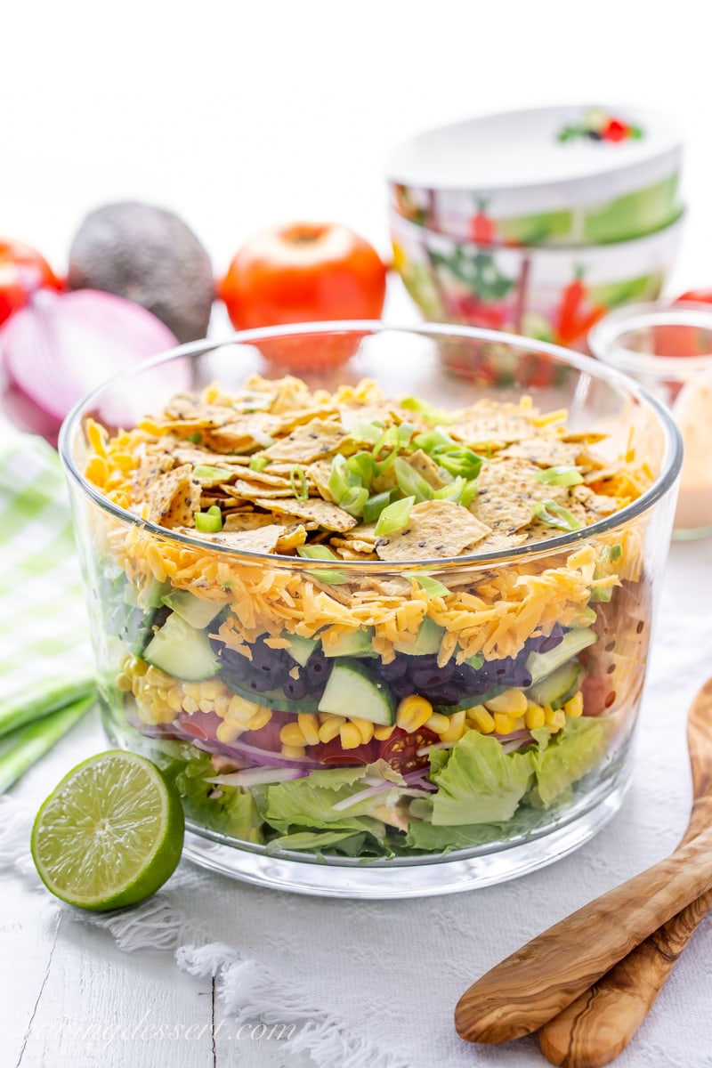 A trifle bowl with a layered Mexican Salad with chips on top