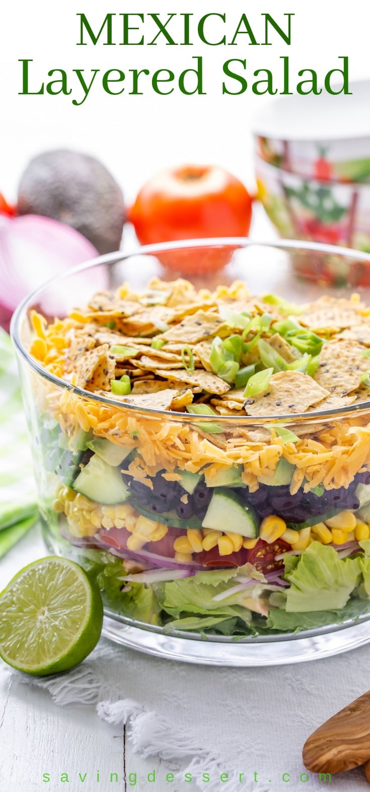 A big glass trifle bowl with a Mexican Layered Salad with lime, chips and shredded cheese