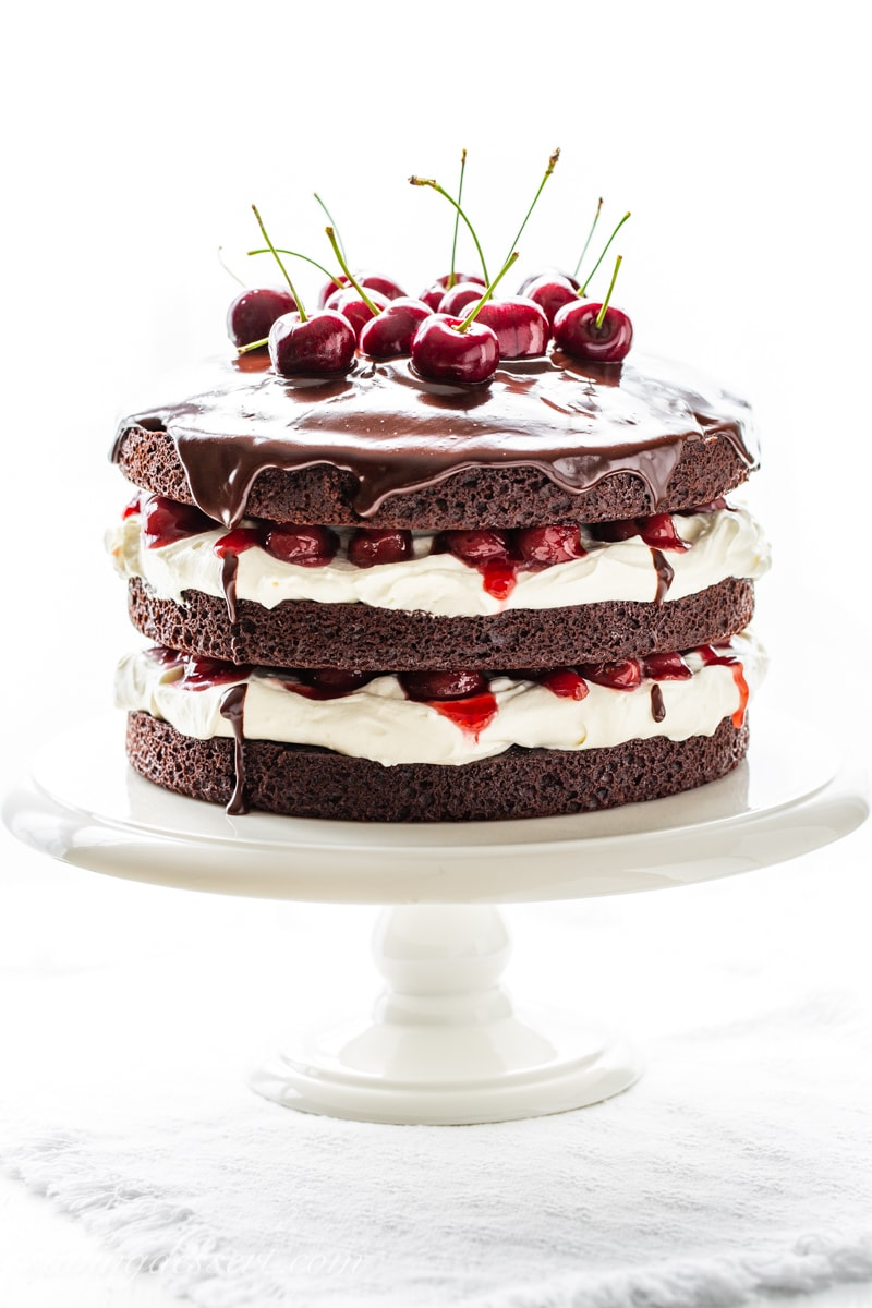 A three layer 'naked' Black Forest Cake with a whipped cream filling and fresh cherry garnish