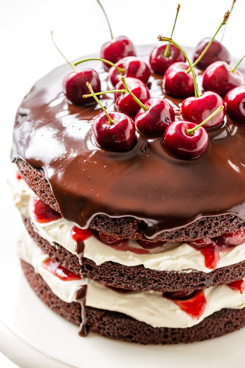A Black Forest Cake topped with a silky chocolate ganache and fresh sour cherries