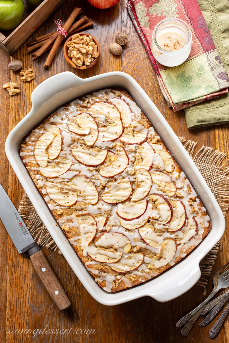 An apple sheet cake covered with sliced apples, drizzled with a simple icing and a sprinkle of cinnamon
