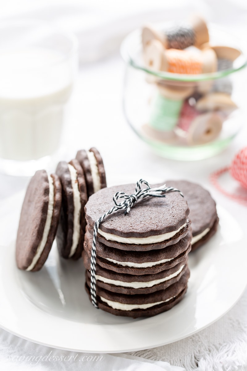 A plate stacked with homemade chocolate sugar cookies with a vanilla cream filling served with a glass of milk