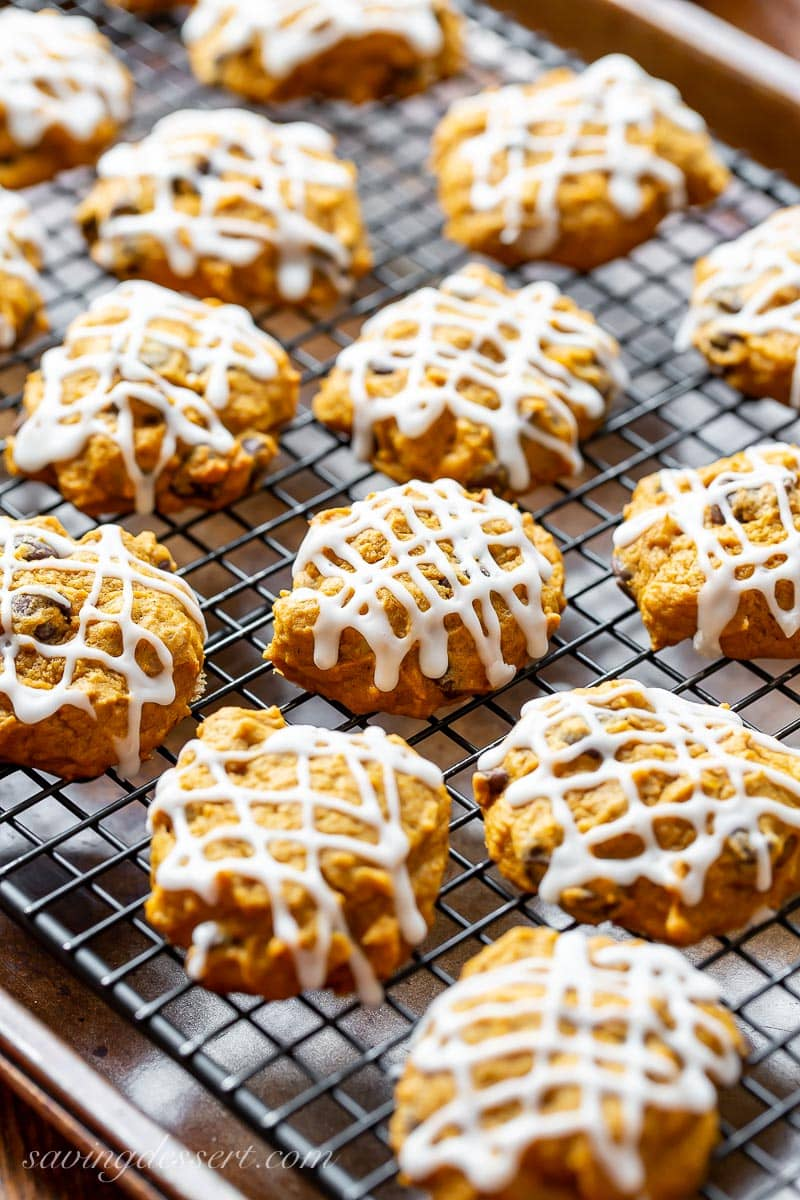 A cooling rack with pumpkin chocolate chip cookies drizzle with icing